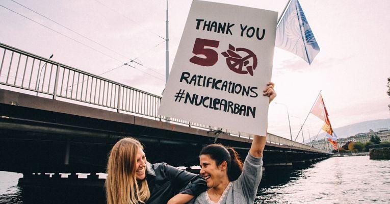 Duas mulheres segurando cartaz de agradecimento