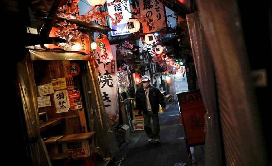 Homem andando em meio a rua de bares em Tóquio