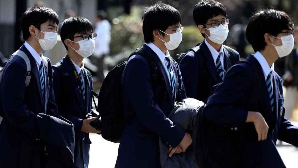 Estudantes japoneses de máscara uniformizados