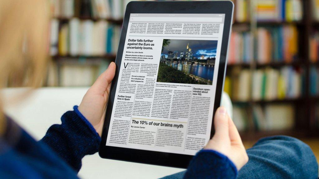 Homem segura tablet para ler notícias