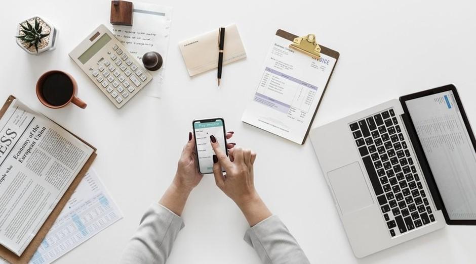 Mesa de trabalho com notebook, celular, jornal e materiais de escritório
