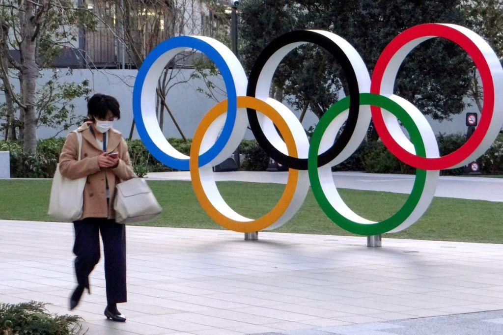 Mulher andando em frente a marco com símbolo das Olimpíadas em Tóquio
