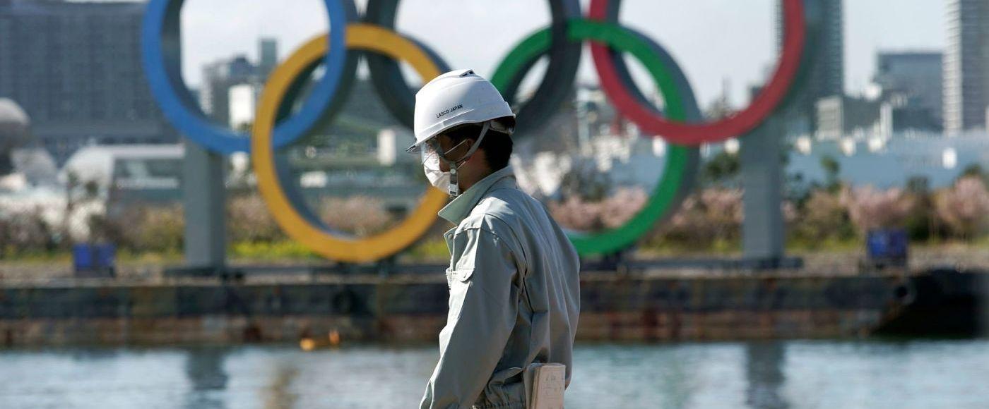 Pessoa andando na frente do símbolo das Olimpíadas