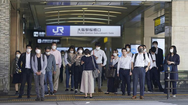 Usuários do sistema de transporte público com máscaras de proteção na saída da Osaka Station