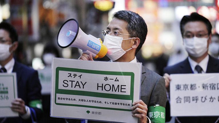 Agentes do governo metropolitano de Tokyo fazendo campanha para as pessoas manterem-se em casa