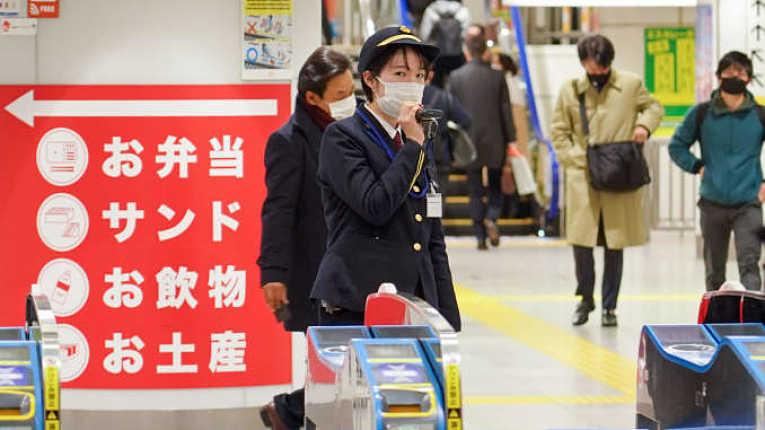 Funcionário de estação de metro de Tokyo com máscara de proteção