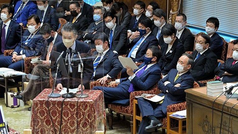 O diretor-geral do Ministério das Comunicações Yoshinori Akimoto (discursando na Câmara dos Representantes na Dieta) é um dos investigados por quebra do código de ética