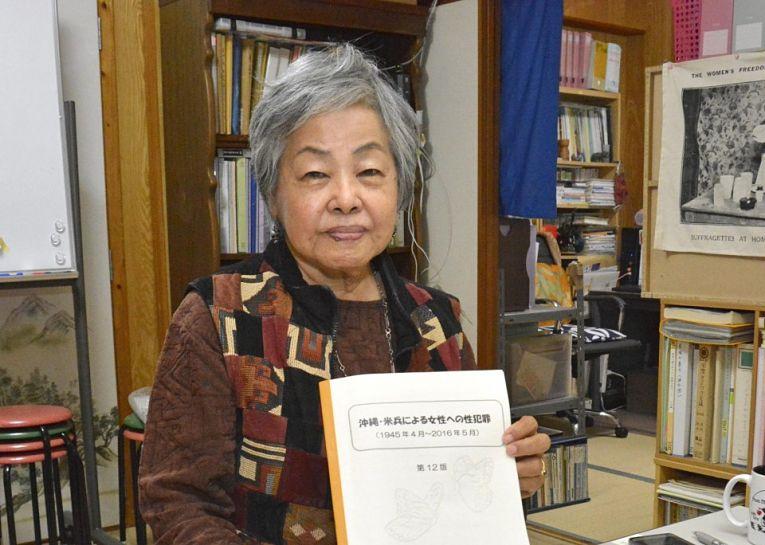 Suzuyo Takazato, copresidente do Okinawan Women Act Against Military Violence com um exemplar do catálogo de crimes 'Postwar U.S. Military Crimes Against Women in Okinawa'