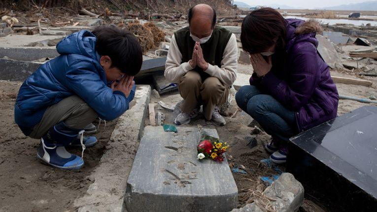 Sobreviventes do terremoto prestam homenagens em túmulo do que sobrou de cemintério