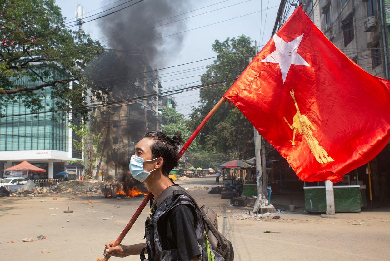 Jovem andando com a bandeira de Myanmar em meio a conflito