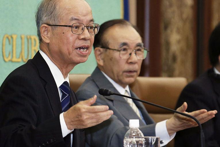 Professor de política pela Kokushikan University Akira Momochi discursando ao microfone do lado esquerdo da imagem