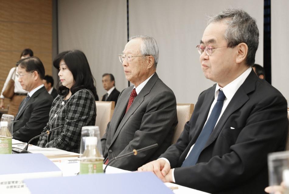 Professor emérito de ciências políticas pela Tokyo University ocupando o último lugar a direita da imagem integrando o painel de consultores durante a abdicação do Imperador Emérito Akihito