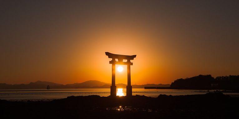 Sol atrás do torri do templo de Nagao