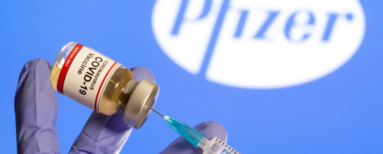 Mãos retiram conteúdo de um frasco de vacina em frente a um logo da Pfizer