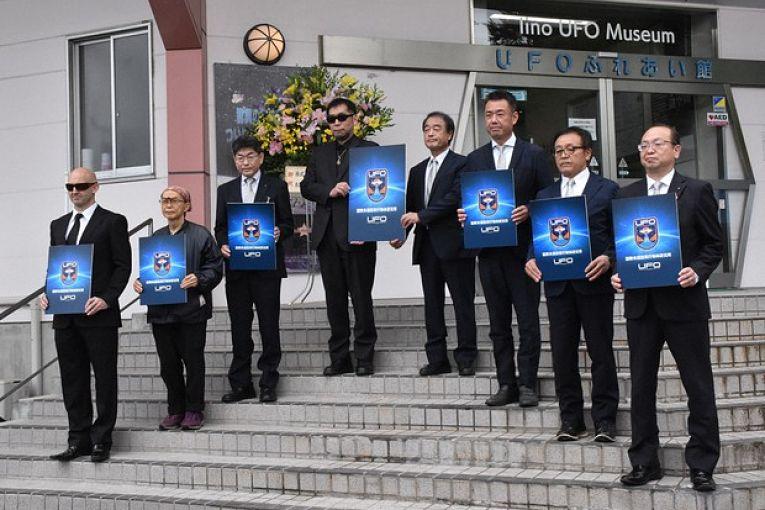 Primeiros associados ao International UFO Lab segurando um cartaz com a insígnia da instituição durante cerimônia de inauguração