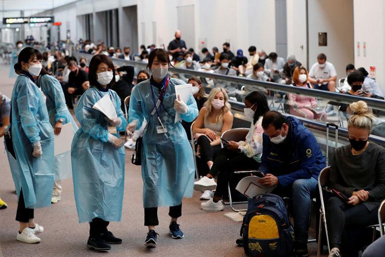 Profissionais de saúde colhem amostras de atletas internacionais no aeroporto de Narita. Foto por  Issei Kato, Reuters