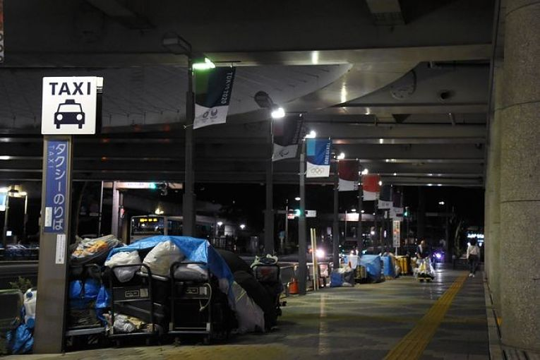 Pessoas em situação de rua em Tokyo dormem embaixo de banners dos Jogos Olímpico
