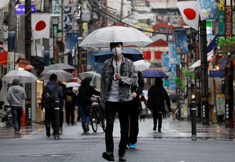 Homem jovem com máscara anda com guarda-chuva em Tokyo em meio a pandemia de coronavírus no Japão